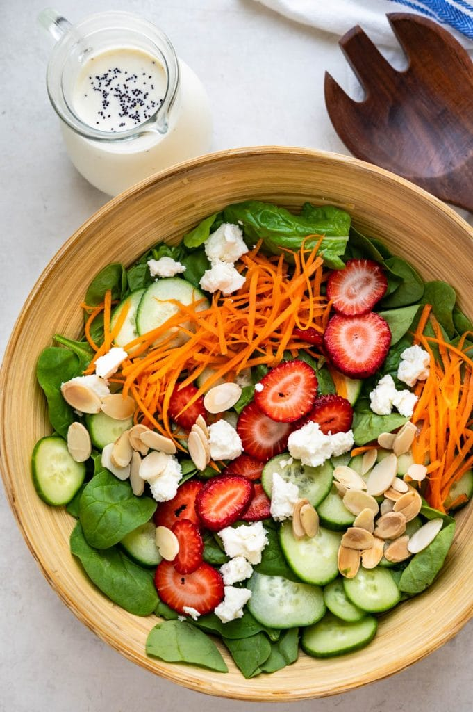 spinach strawberry salad with poppy seed dressing on the side.