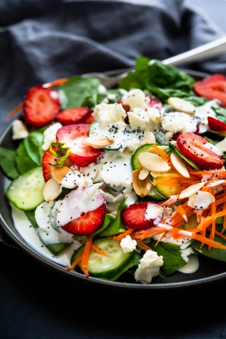 A dressed plate of strawberry and spinach salad with carrots, almonds and crumbled cheese.