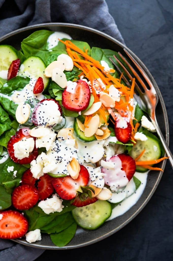 an overhead shot of the summer strawberry salad on a plate with dressing.