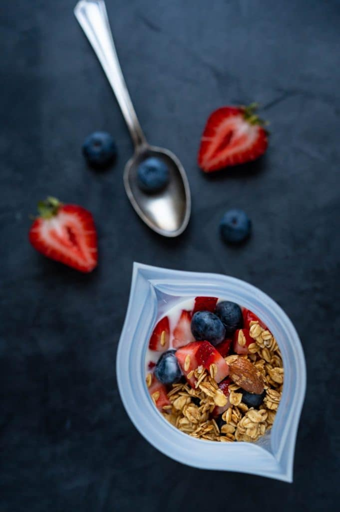 Filling a cup shaped silicone storage bag with granola and yogurt with berries for an on the go breakfast.