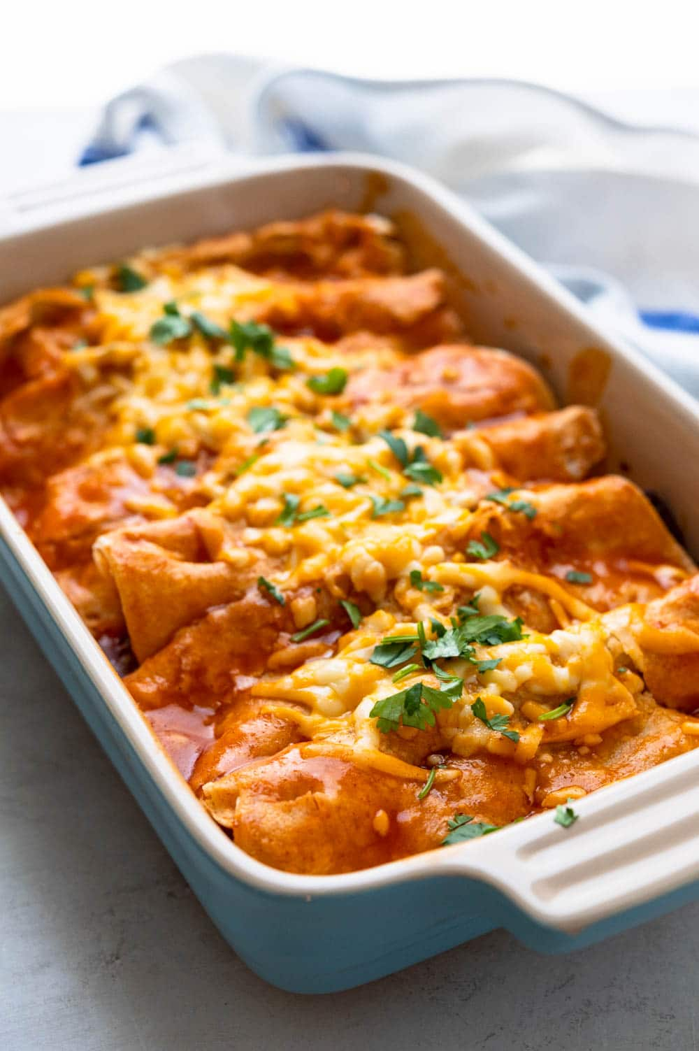 A baked beef enchilada casserole garnished with chopped cilantro.
