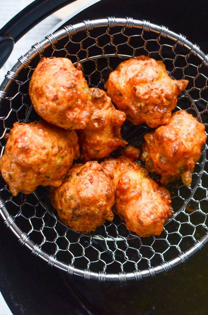 scooping authentic bahamian conch fritters out of the fryer.