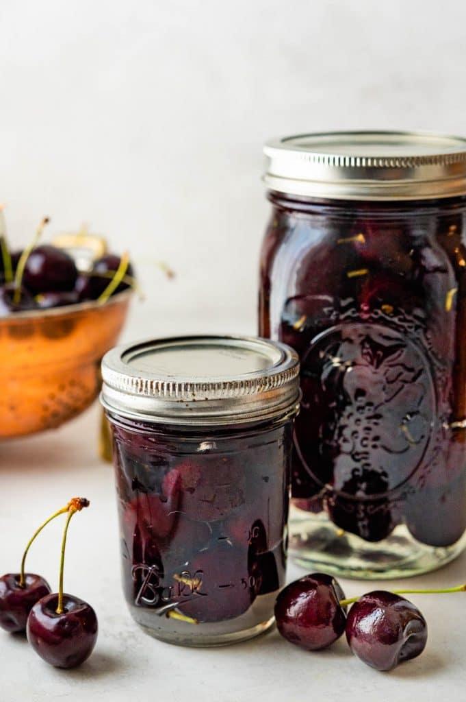 Two sizes of drunken cherries in jars, before the long soak.