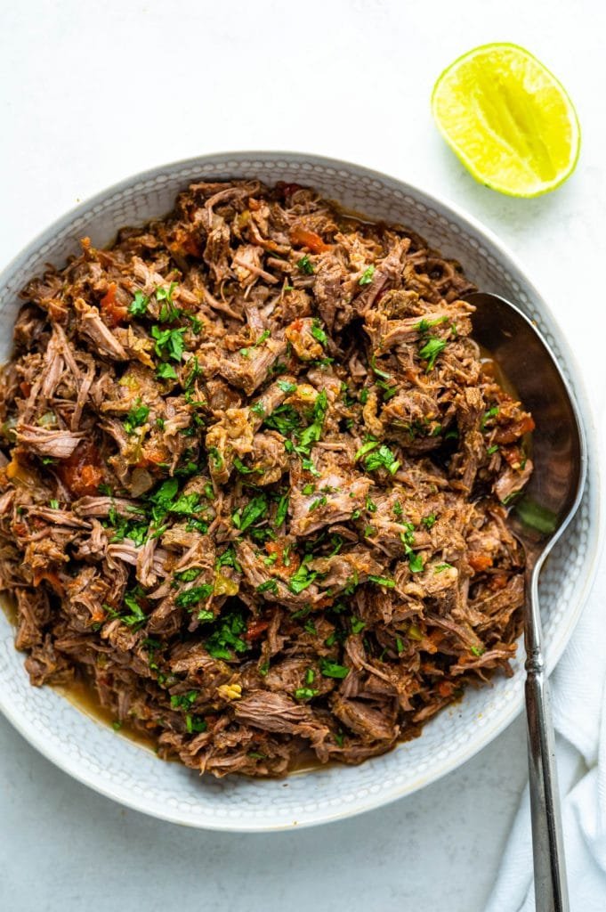 Mexican pulled beef with a lime wedge and cilantro.