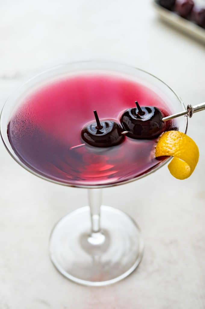 a luminescent cherry red martini with garnish.