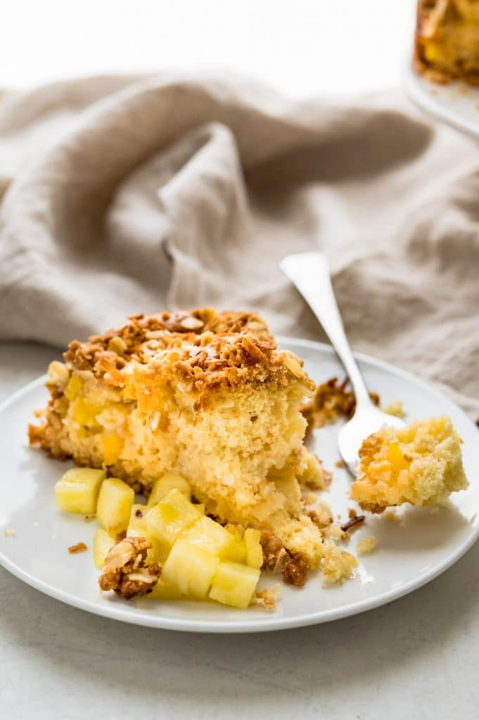 a slice of pineapple coconut coffee cake with extra pineapple on the side.