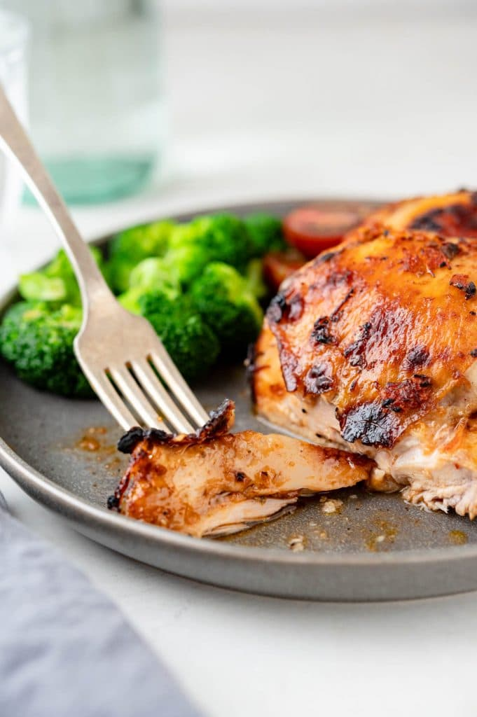 Cutting into juicy baked chicken thighs with chipotle marinade.