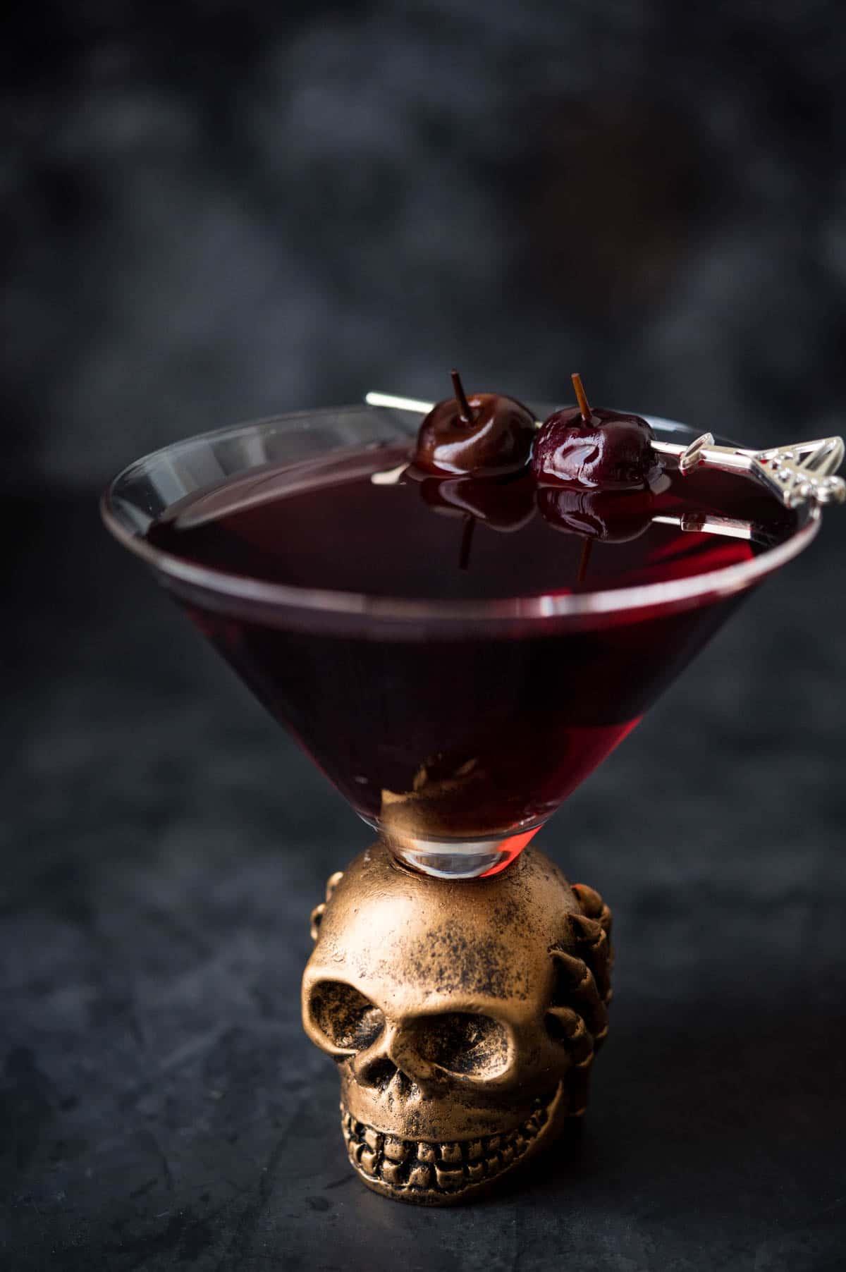 spooky halloween drunken cherry martini in a skull glass.