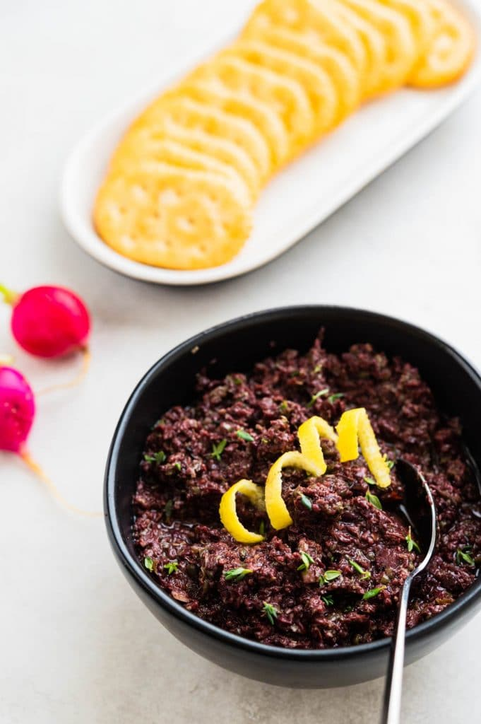 a bowl of black olive tapenade to spread on crackers or dip crudite into.
