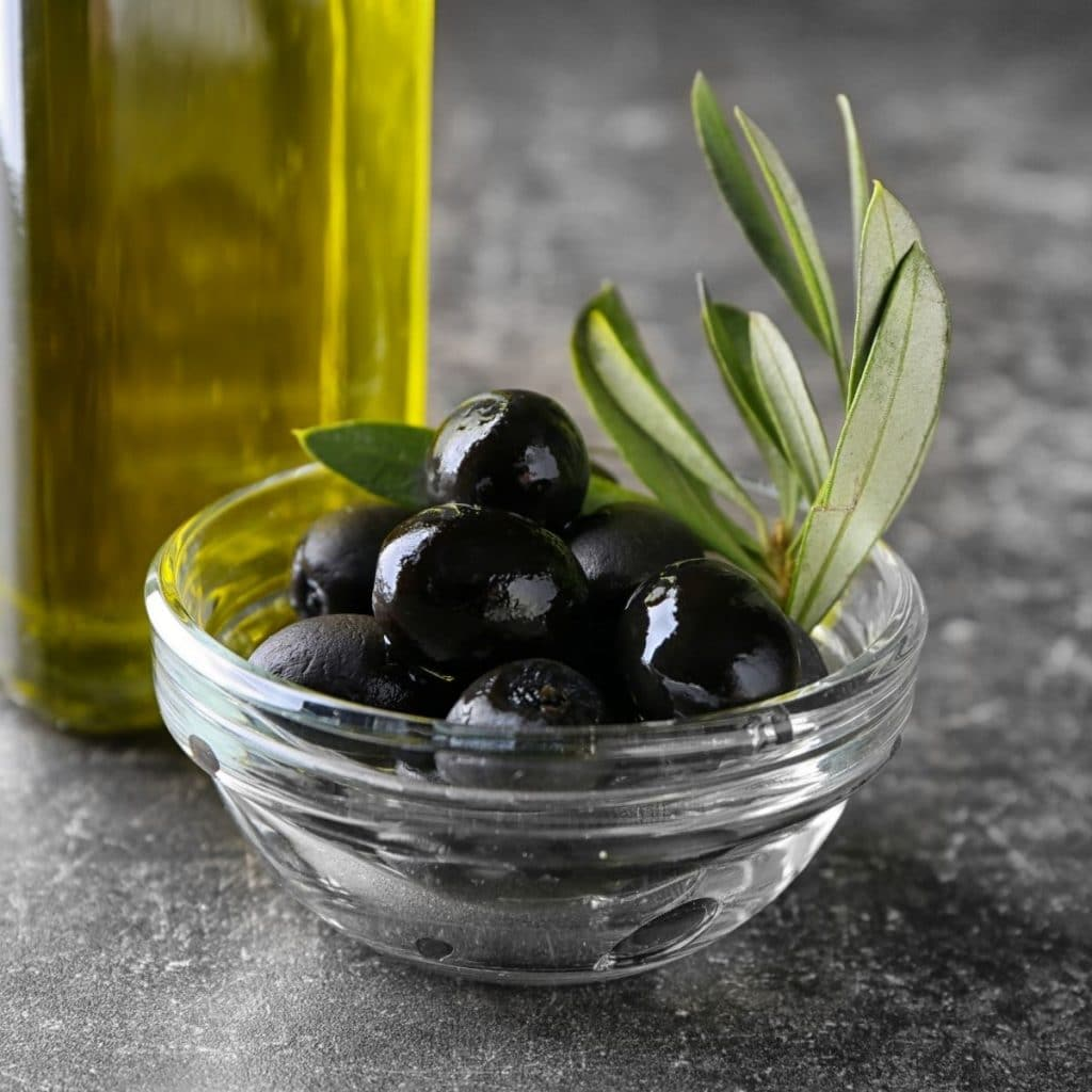 a bowl of black olives with olive oil in the background.