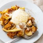 a serving of apple brown betty with a scoop of ice cream.