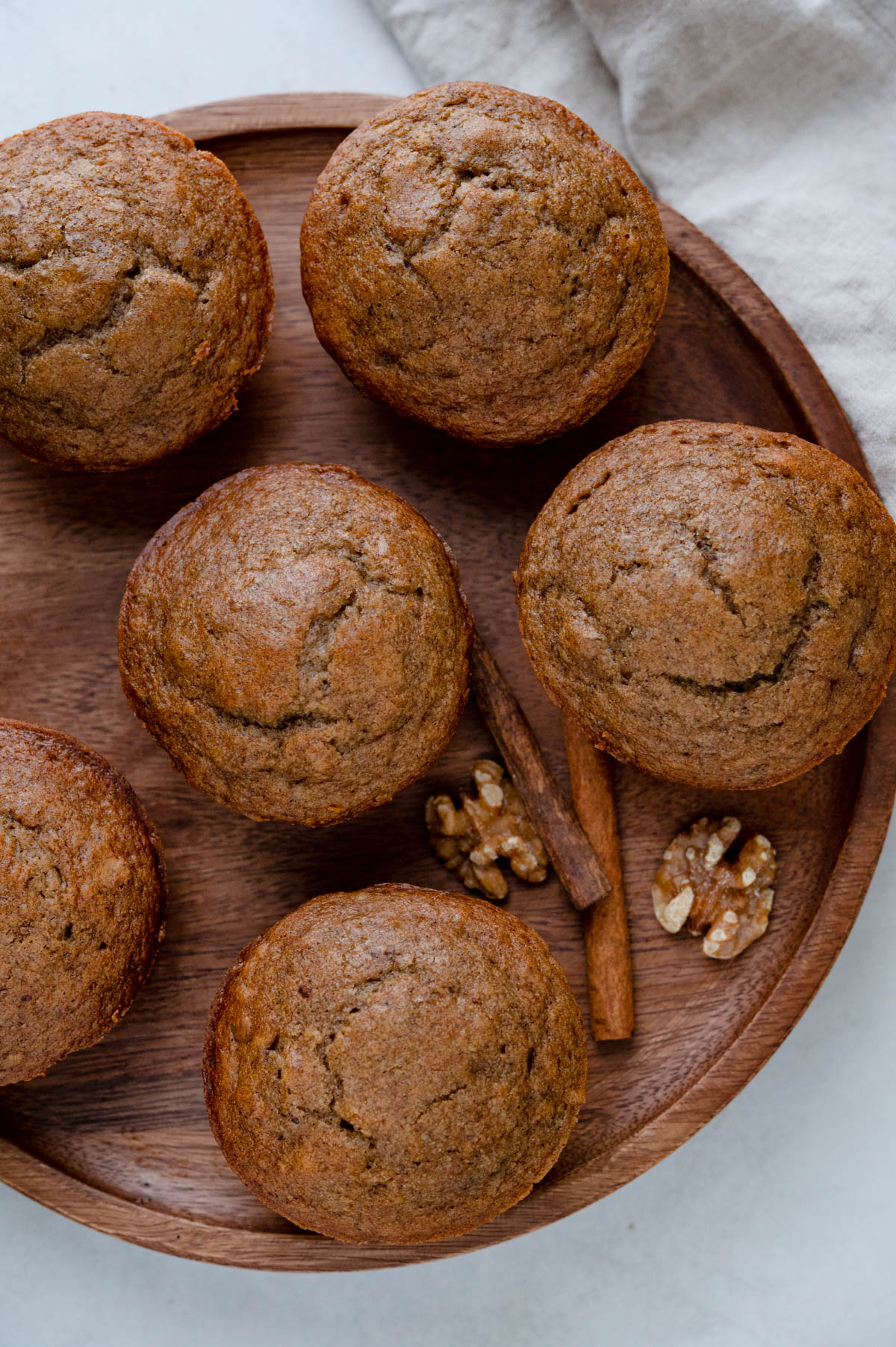 a wooden cake platter filled with apple walnut muffins.