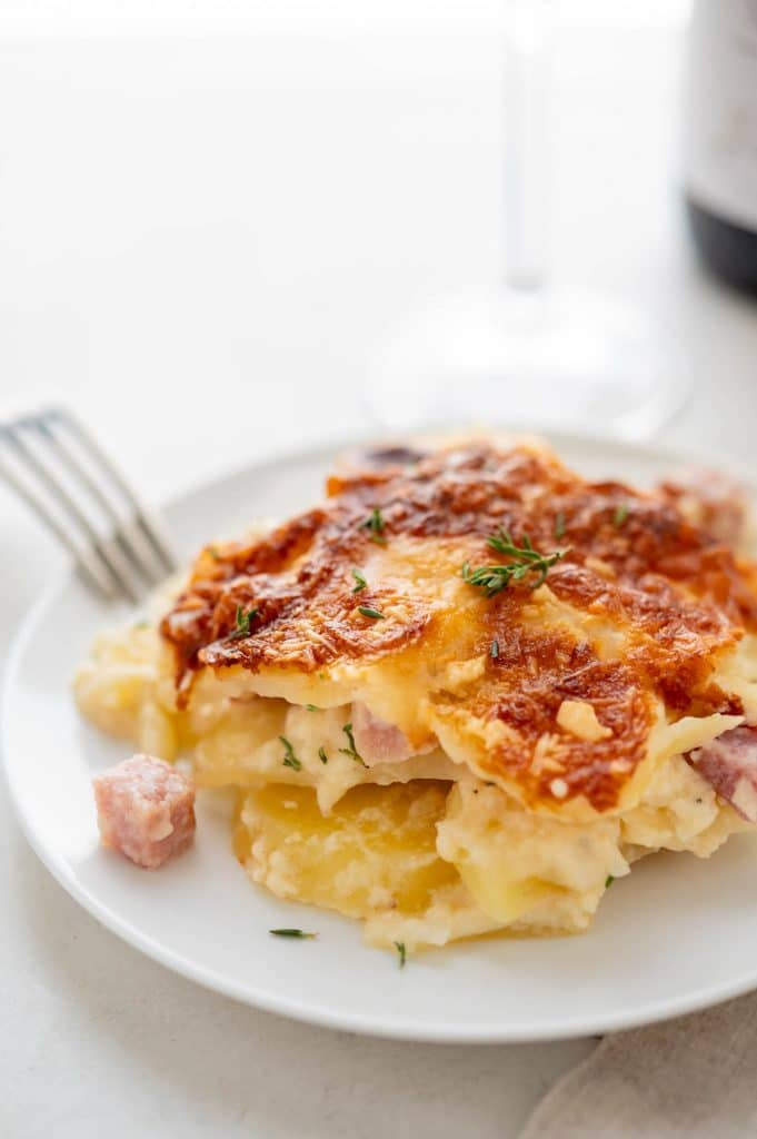 A serving of cheesy scalloped potatoes with ham on a plate with a fork.