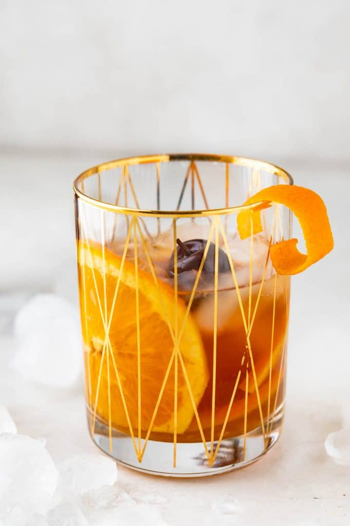 Holiday spiced old fashioned in a gold rimmed glass with orange slice, cherry and twist.